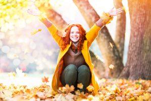 Frau wirft Bltter im Herbst